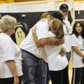 Coach Rochelle Kabisch hugs Benton Easter, stepfather of Jessica Rogers, as father Doug Rogers and fiancee Amy, and Jessica's mother Margie Easter (far right) look on during a memorial on Saturday. Henrietta High School retired the No. 17 jersey of Rogers following Henrietta's win over jacksboro.