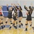 Henrietta's Lady Cats celebrate a block during the first set of Monday night's Region I quarterfinal. Despite taking on the role of underdog, Henrietta opened the match with a win and eventually forced a fifth set.