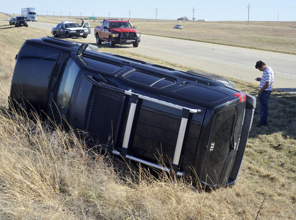 Marco Morales of Fort Worth makes a phone call after rolling his vehicle near Henrietta Monday. Morales was traveling for Fort Worth to Wichita Falls.