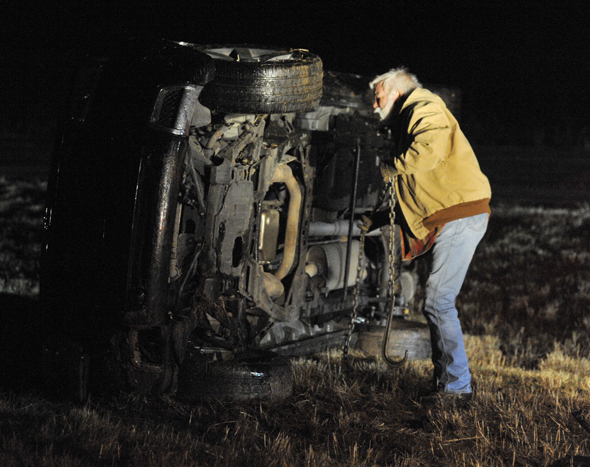 Larry Crowley of Accent Auto Body hooks chains to a vehicle that rolled over on Hwy. 287 early Tuesday morning. The driver, Christopher Wayne Shelton of Vernon, and a passenger were not injured.