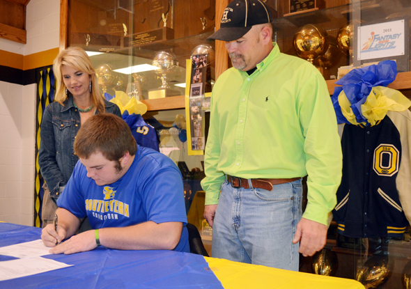 Parents Carrie and Byron West look on as Henrietta lineman Parker West signs a letter of intent Wednesday to play football at Southeastern Oklahoma State University.