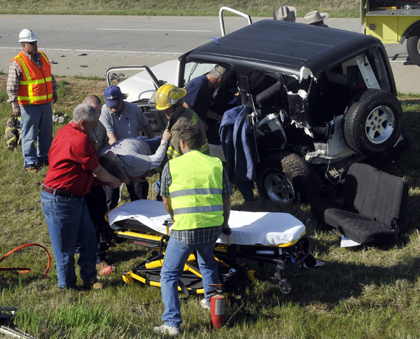 Henrietta fire fighters and EMTs extract a woman from one of two vehicles involved in a wreck Monday on Hwy. 287 south of Henrietta.