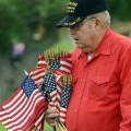 Zirl Rogers of Henrietta, a member of Bucky Boyd Post 5401 and Vietnam veteran, carries bundles of U.S. flags to be placed at the graves of veterans buried in Hope Cemetery.