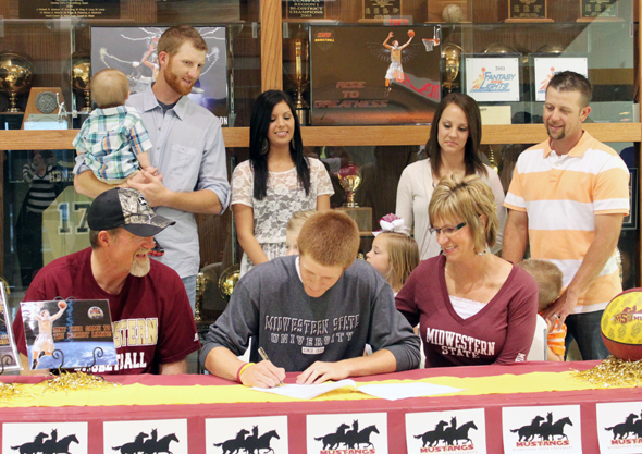 Henrietta senior Nick Powell, surrounded by family members, signs a letter of intent to play basketball for Midwestern State University.