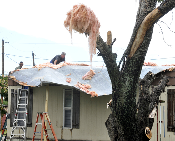Ken Marshall works on his home on East Fourth Street in Henrietta Monday after a strong thunderstorm tore the roof from the house in the early morning hours.