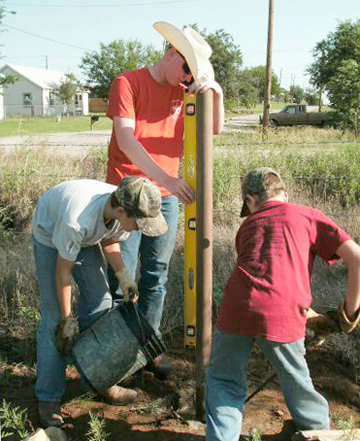Eagle Scout Luke Brock, Boy Scout Corbin Cody and Cub Scout Carson Cody set a corner post for a fence to go up around the future home of Boy Scout Troop 91 and Cub Scout Pack 92. The new property is located on West Travis Street, at the south end of Bridge Street, in Henrietta.