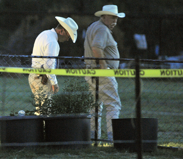 Texas Ranger Marshall Thomas and CCSO Chief Deputy Mark Elgin search for evidence in the backyard of a residence in Deer Creek, where a young boy was shot Friday afternoon.