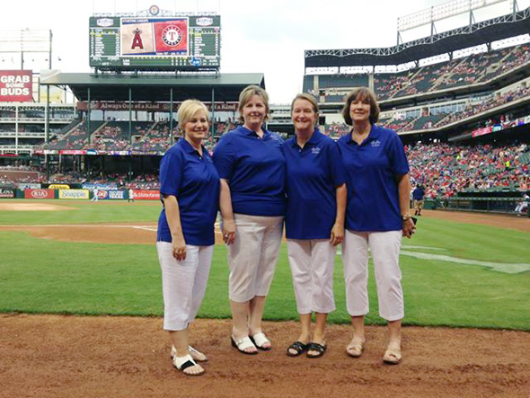 "Penny Riordan, Laura Lee Brock, Diane Hanson and Laurie Schaffner of the group ""One Voice"" gather on the field at the Ballpark in Arlington before performing the national anthem."