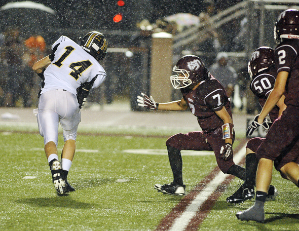 Henrietta Quarterback Conner Fletcher scrambles to escape a trio of Bowie defenders in the backfield Friday night.
