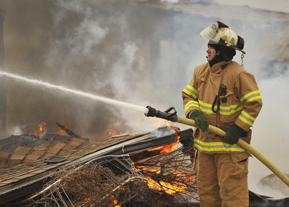 Drew Franklin, assistant chief of the Lakeside City VFD, fights a blaze that claimed the home of Thomas Steidl, a member of the Arrowhead Ranch Estates VFD, Thursday morning.