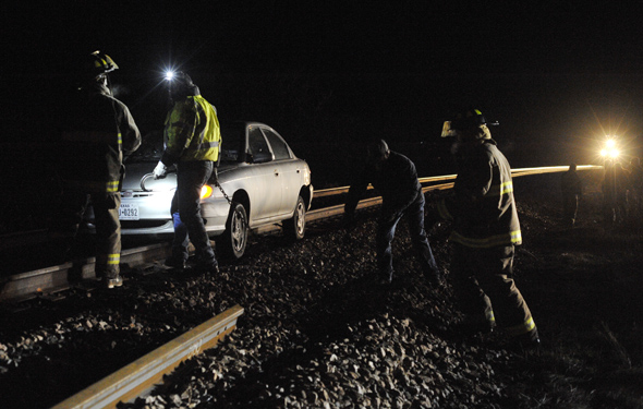 A train is stopped in west Henrietta Thursday night while a car is removed from the railroad tracks. The driver of the vehicle was not injured in the accident.