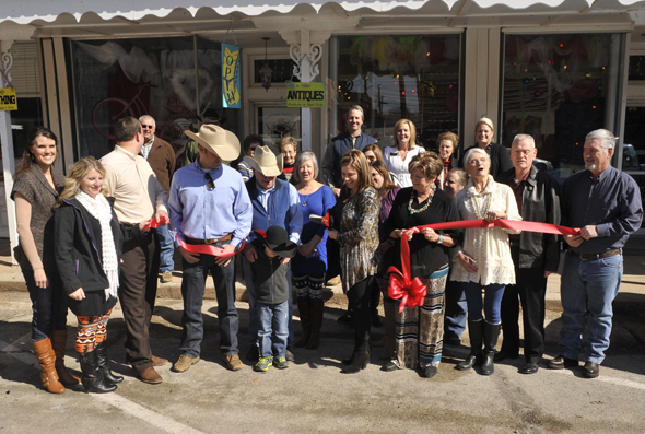 Coye, Lacy and Pate Cody of Cow Palace Couture are joined by directors of the Henrietta and Clay County Chamber of Commerce, City of Henrietta representatives, vendors, friends and family during a ribbon cutting ceremony Wednesday.