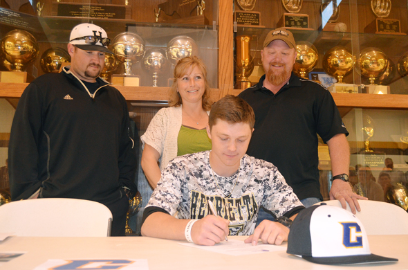 Tylor Brown signs a letter of intent to play baseball for Central Christian College of Kansas as Henrietta Baseball Coach Kyle Sims and parents Nancy and Jeff Brown look on.