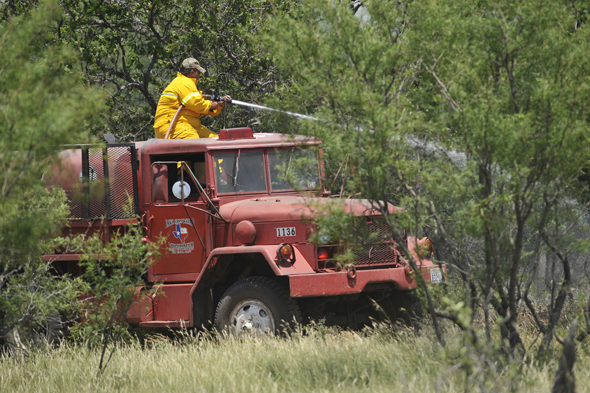 A Lake Arrowhead VFD unit is steered through heavy mesquite growth while battling a blaze southwest of Henrietta Monday afternoon.