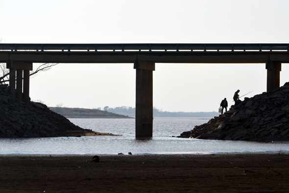 Two men look for a place to fish under the Henrietta bridge on the east side of Lake Arrowhead. As of Monday, the Reservoir is at 22.1 percent capacity.