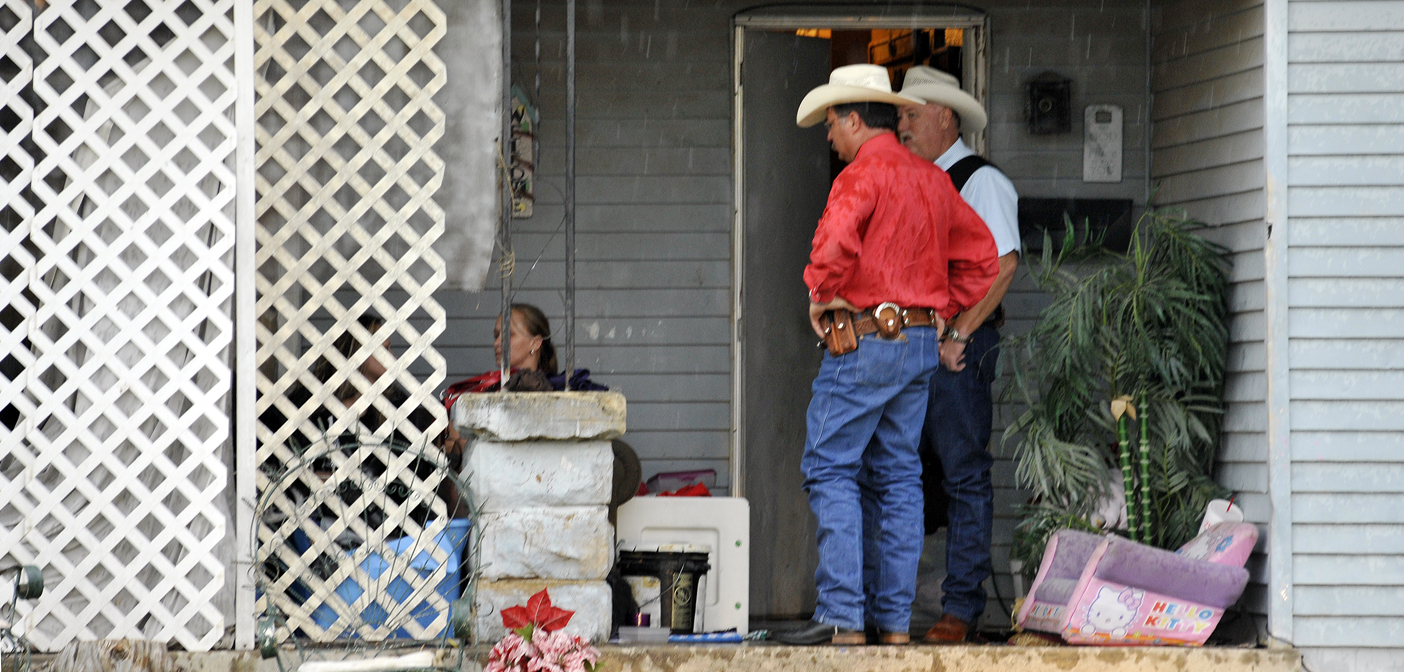Sheriff Kenny Lemons and Chief Deputy Mark Elgin question Krisha Wolf (hidden behind a lattice) and another woman as Wolf's residence in Henrietta is searched by deputies.