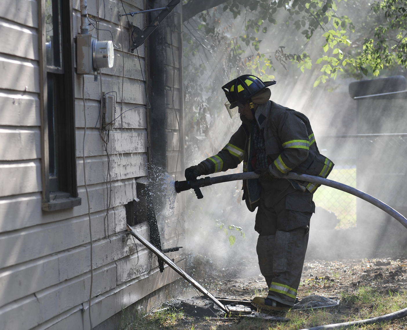 HVFD Fire Fighter Greg Borgman soaks a portion of an exterior wall that was cut away while battling a house fire in Henrietta Monday morning.
