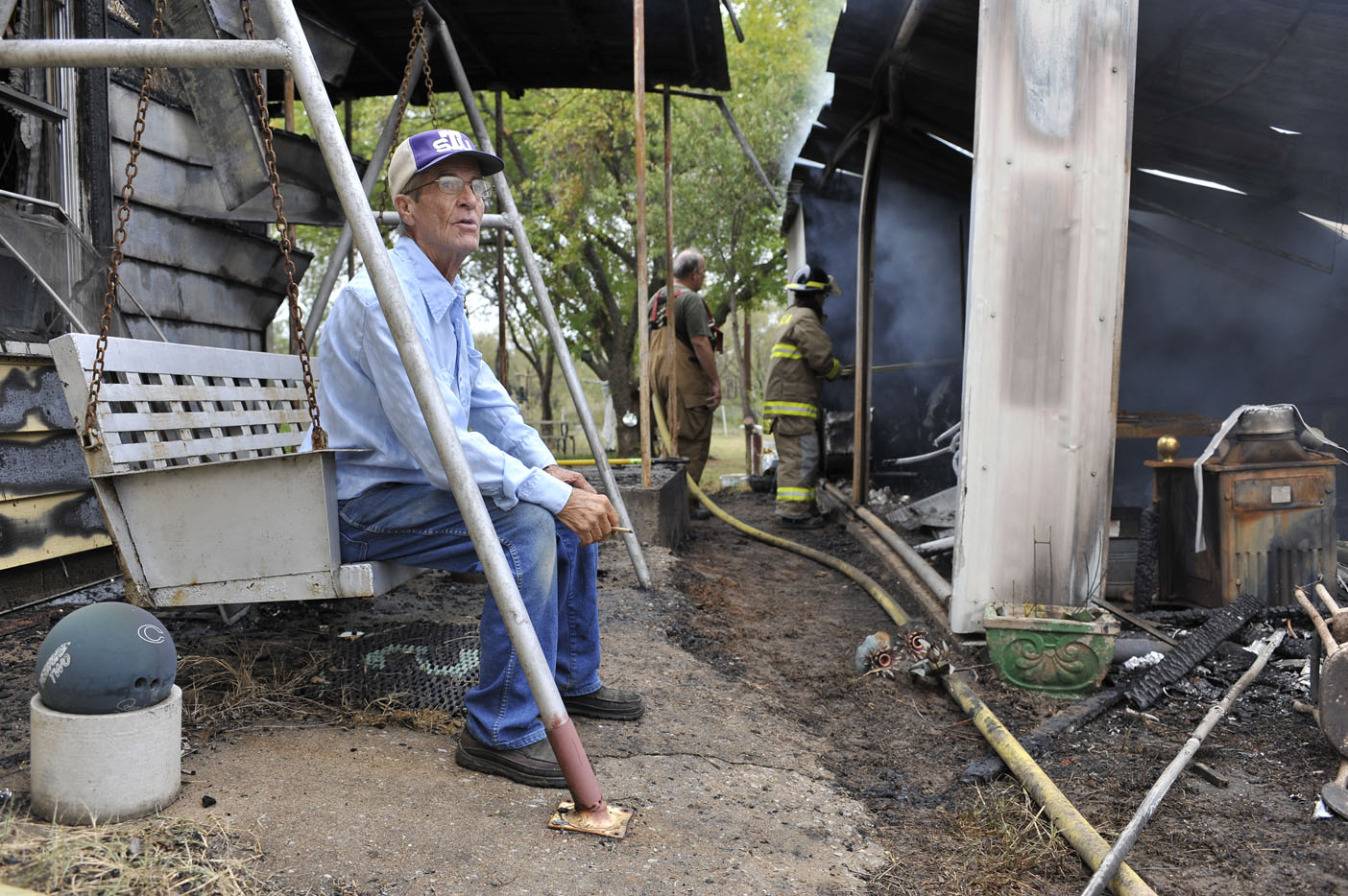 Property owner William Caddell of Petrolia looks on as PVFD Fire fighter Marilyn Loucks uses a pike pole to locate hotspots in Caddell's garage Thursday after an early morning structure fire in Petrolia.