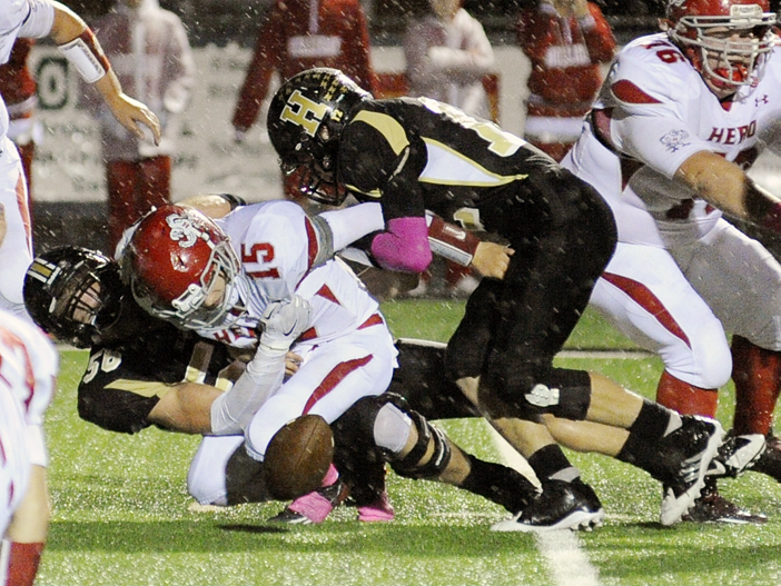 Bearcats Logan Carter and Dylan Galyean sack Holliday quarterback Levi Draper during Friday's weather-delayed win over the Eagles. The Henrietta defense limited Holliday to 137 yards of offense.