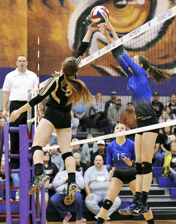 Henrietta junior Kenzie Kirk dinks the ball past a Peaster blocker in the first set of Saturday's area volleyball playoff. The Lady Cats fell in three sets.