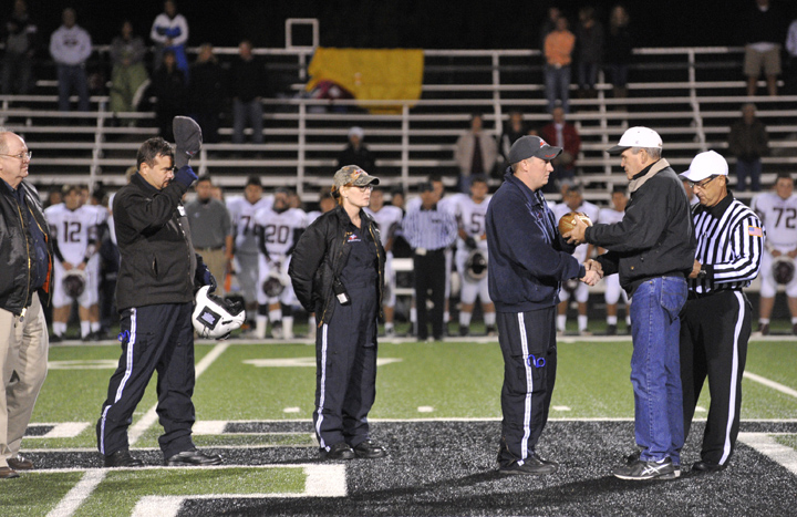 Air Evac Program Director Roger Ritchie, pilot Chris O'Brien, flight nurse Keri Arrelano and flight medic Johnny Cendroski are presented a signed game ball by High School Principal Gary Parrish during Friday's memorial for the two members of Life Team 25 who died in an Oct. 4 helicopter crash.