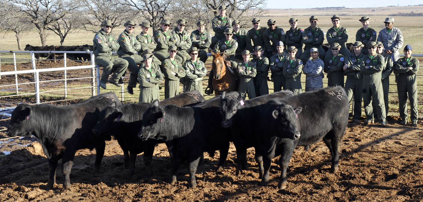 The 469th Flight Training Squadron from Sheppard Air Force Base pose for a photo with Angus bulls at Pullen-Mayfield Ranch.